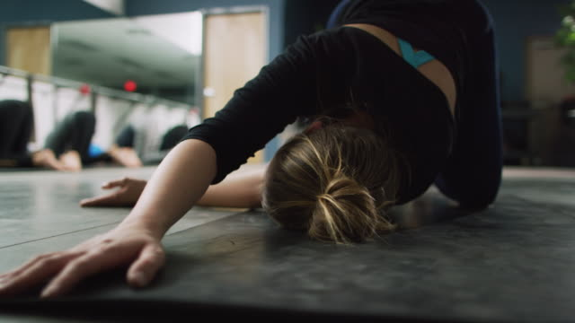 a caucasian female fitness instructor in her twenties stretches on a yoga mat for her class in an exercise studio - pilates stock videos & royalty-free footage