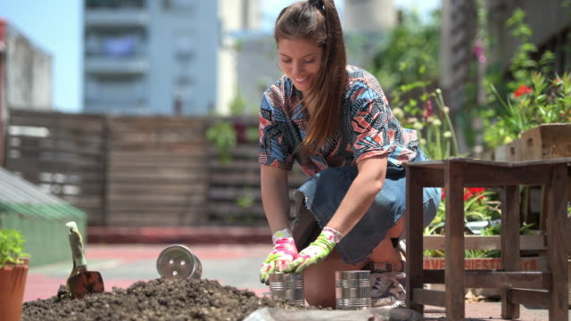 caucasian female gardener filling can with soil for planting - wellbeing stock videos & royalty-free footage
