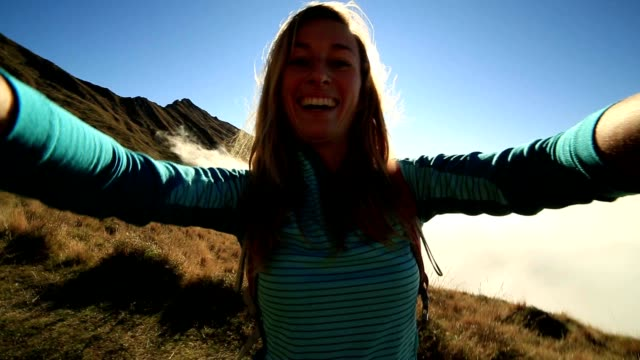 Caucasian female hiking takes selfie above the clouds