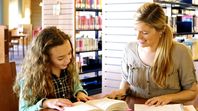 caucasian female home school elementary student read to her caucasian mid-adult mother or tutor - help single word stock videos and b-roll footage