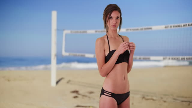 caucasian female in her 20s wearing bikini at beach next to volleyball net - volleyball net stock videos & royalty-free footage