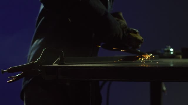 a caucasian female in her thirties uses an electric angle grinder to smooth a weld as sparks fly in a workshop - gender equality stock videos & royalty-free footage