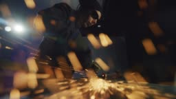 A Caucasian Female in Her Thirties Uses an Electric Angle Grinder to Smooth a Weld as Sparks Fly in a Workshop