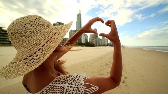 Caucasian female in Surfers Paradise makes heart shape finger frame