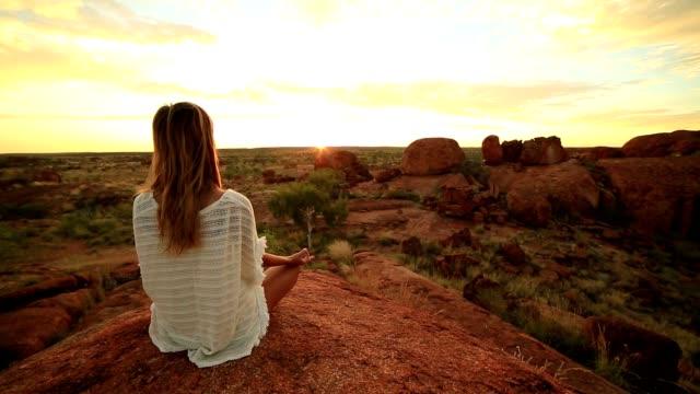 Caucasian female meditating at sunrise
