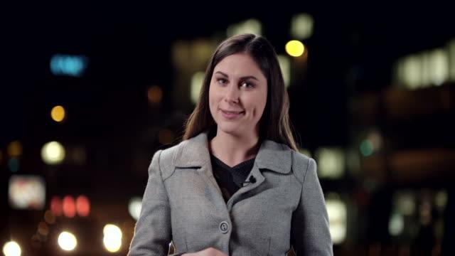 Kaukasische weibliche News-Reporter Berichten aus der Stadt in der Nacht
