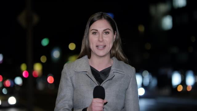 vídeos de stock, filmes e b-roll de caucasiano feminino repórter ao vivo no estúdio da cidade à noite - jornalista