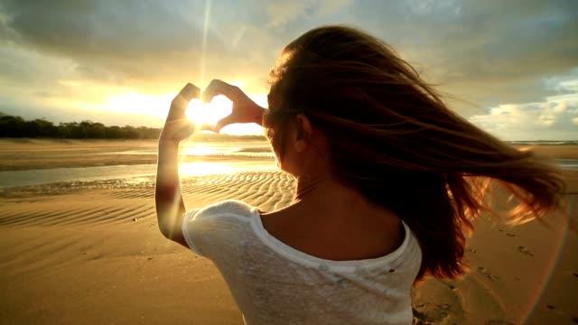 Kaukasische Weibchen am Strand macht Herzen Formrahmen finger