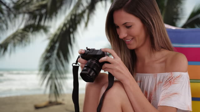 Caucasian female photographer in her 20s taking picture at tropical beach