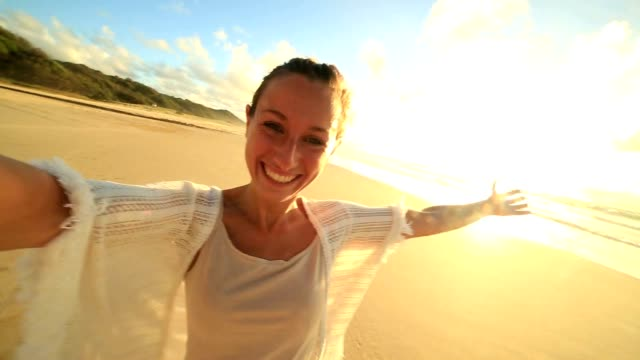 Caucasian female takes selfie portrait on beach at sunset