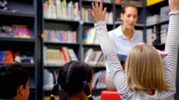 Caucasian female teacher teaching schoolkids in the school library 4k