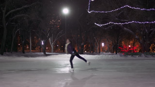 caucasian female teenager skates with joy on a snowy night.. - ice skating stock videos & royalty-free footage