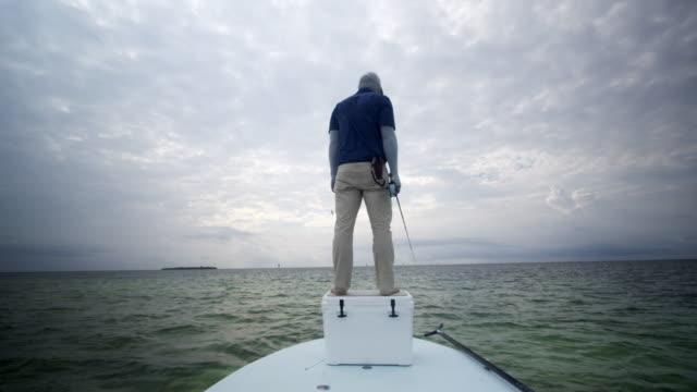 vídeos de stock, filmes e b-roll de caucasian fisherman fly fishing on skiff boat - calça comprida
