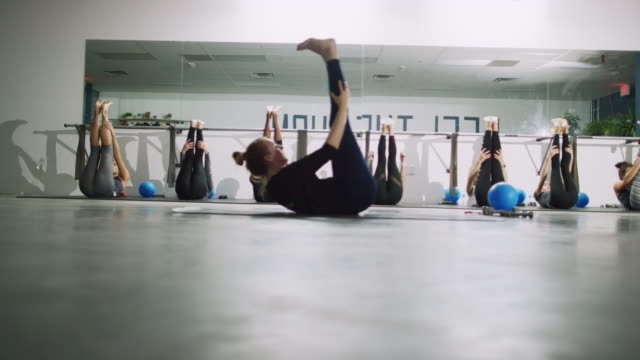 a caucasian fitness instructor in her twenties models raising her legs in the air while laying down and pulsing crunches for her multi-ethnic class of women in an exercise studio - pilates stock videos and b-roll footage