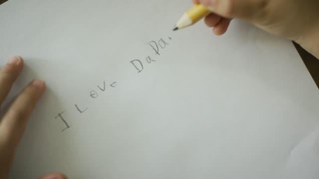 """vídeos y material grabado en eventos de stock de una mano del caucásico de cinco años escribe """"me encanta dada"""" en lápiz en un pedazo de papel - ortografia"""
