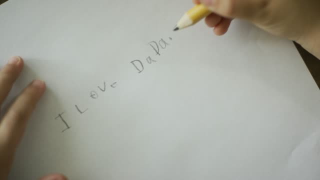 "vídeos de stock e filmes b-roll de a caucasian five year-old's hand writes ""i love dada"" in pencil on a piece of paper - soletrar"