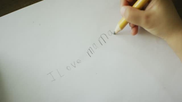 白人の5歳の手が、紙に鉛筆で「私を愛するママ」と書いている - 学校備品点の映像素材/bロール