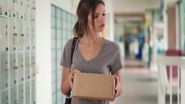 stockvideo's en b-roll-footage met caucasian girl checking package before heading to post office in post office - lockerkast
