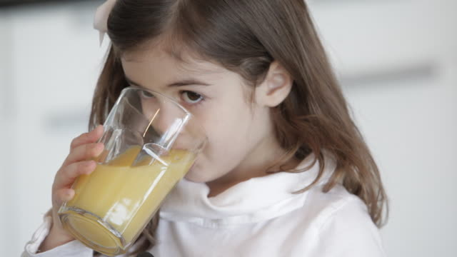 Caucasian girl drinking orange juice
