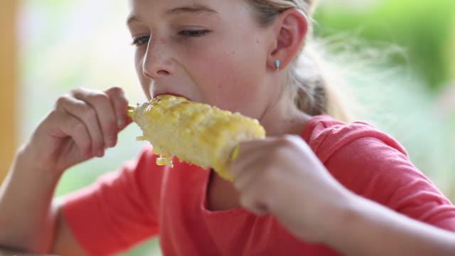 Caucasian girl eating corn on the cob