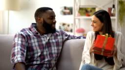 Caucasian girl giving gift box to her Afro-American boyfriend, birthday greeting