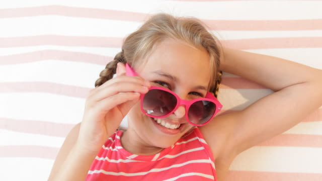 Caucasian girl on beach towel peering over sunglasses