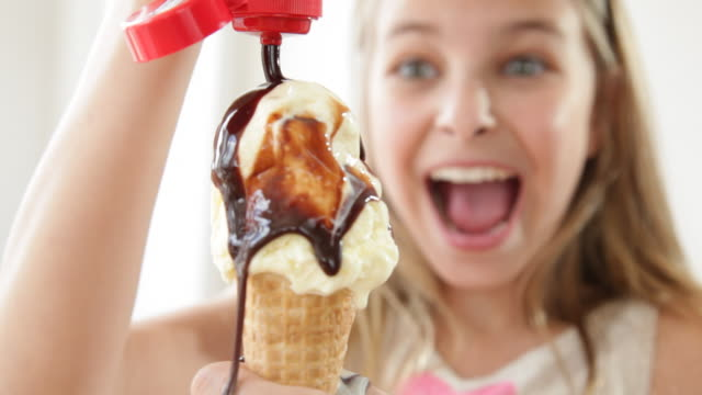 caucasian girl pouring chocolate syrup over ice cream cone - waffle cone stock videos and b-roll footage