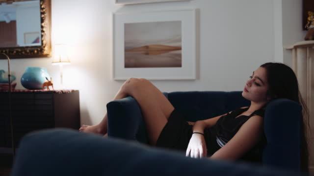 vídeos de stock, filmes e b-roll de caucasian girl relaxing in armchair with feet up - pré adolescente
