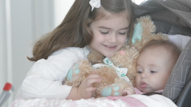 caucasian girl smiling at baby sister in stroller - soft toy stock videos & royalty-free footage