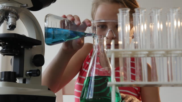 vídeos de stock e filmes b-roll de caucasian girl using microscope and experimenting with liquid - só uma rapariga