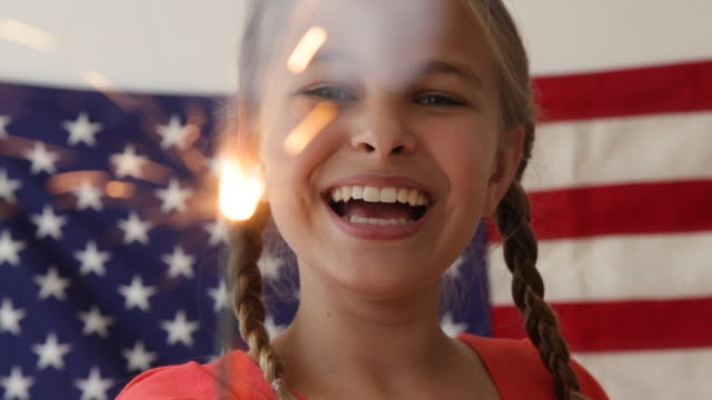 caucasian girl waving sparkler near american flag - fourth of july stock videos and b-roll footage