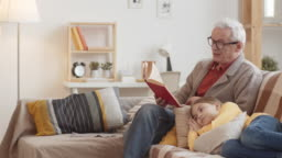 Caucasian Granddad Reading Aloud Book and Girl Listening