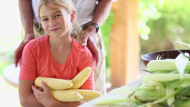 caucasian grandfather and granddaughter smiling with corn - husking stock videos & royalty-free footage