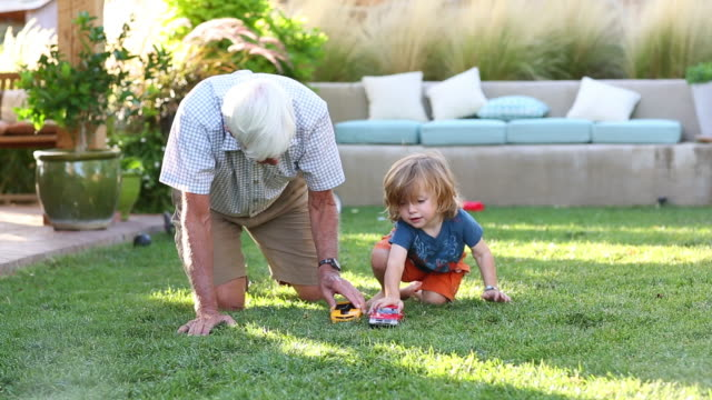 Caucasian grandfather and grandson playing in backyard