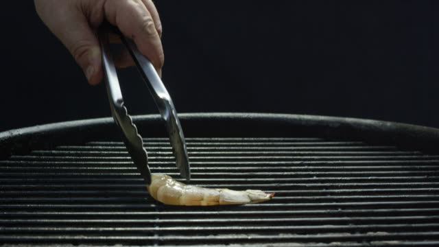 caucasian hand places a single shrimp onto a metal grate barbecue grill with serving tongs - serving tongs stock videos & royalty-free footage