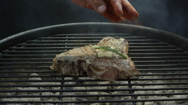 白人手のバーベキュー グリルでバターとローズマリーの熱い石炭の t ボーン ステーキに調味料をふりかけてください。 - ローズマリー点の映像素材/bロール