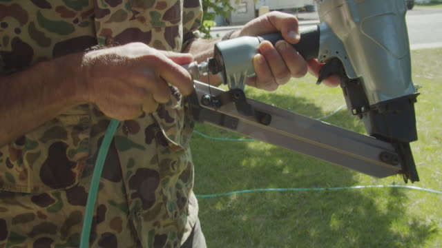 a caucasian handyman attaches an air hose to a pneumatic nail gun in a residential neighborhood outdoors on a sunny day - accuracy stock videos & royalty-free footage