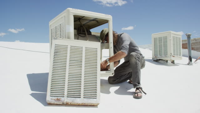 a caucasian handyman in his forties applies white plumbers tape to the inside of a rooftop swamp cooler while getting it ready for use on a sunny day - plumber stock videos & royalty-free footage