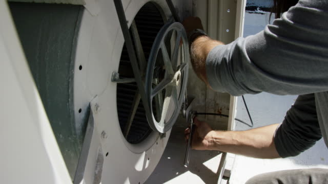 a caucasian handyman in his forties uses an adjustable wrench to tighten a connection inside a rooftop swamp cooler while getting it ready for use on a sunny day - motor stock videos & royalty-free footage