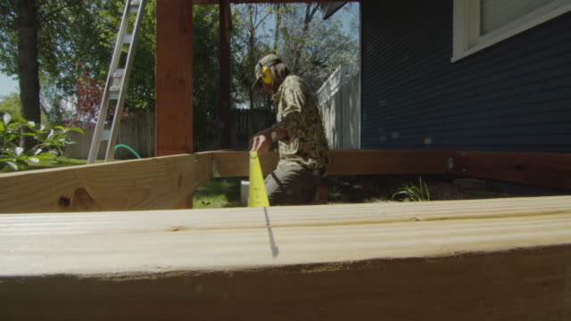 a caucasian handyman in his forties wearing a hat, hearing protection, sunglasses, and kneepads uses a tape measure to measure in between two wooden boards while building a deck in a residential neighborhood outdoors on a sunny day - measuring stock videos & royalty-free footage
