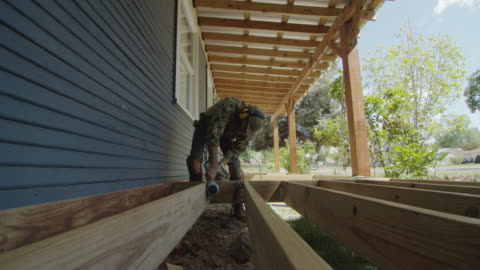 a caucasian handyman in his forties wearing a hat, hearing protection, and kneepads uses a pneumatic nail gun to secure metal corner brackets on wooden boards while building a deck in a residential neighborhood outdoors on a sunny day - construction industry stock videos & royalty-free footage