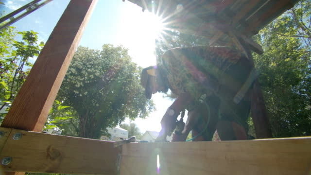 a caucasian handyman in his forties wearing a hat, sunglasses, hearing protection, and kneepads uses a pneumatic nail gun to secure metal corner brackets on wooden boards while building a deck in a residential neighborhood outdoors on a sunny day - patio stock videos & royalty-free footage