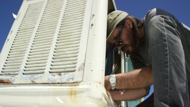 a caucasian handyman in his forties with a beard removes a swamp cooler side panel and applies white plumbers tape to the inside of the unit while getting it ready for use on a sunny day - plumber stock videos & royalty-free footage