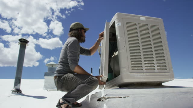 a caucasian handyman in his forties with a beard replaces the side panel of a swamp cooler on a rooftop on a sunny day - repairing stock videos & royalty-free footage