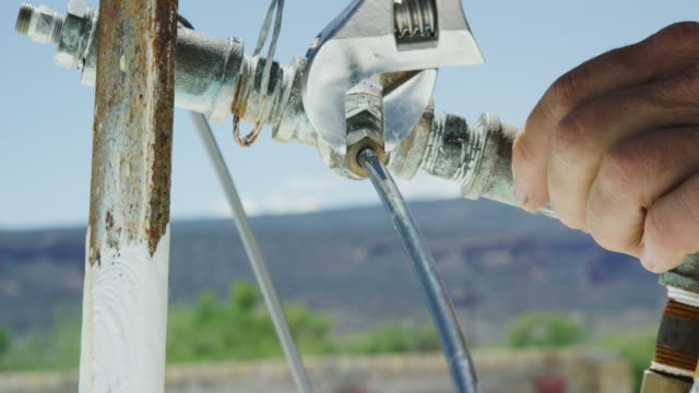 a caucasian handyman tightens the nut on a water line using his fingers and then an adjustable wrench while getting a swamp cooler ready for summer on a rooftop on a sunny day - plumber stock videos & royalty-free footage