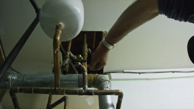 a caucasian handyman turns on the water for a swamp cooler system by turning a lever in a garage indoors - repairman stock videos & royalty-free footage