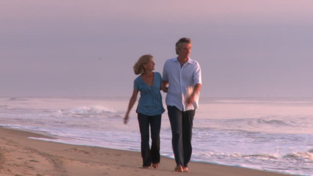 caucasian husband and wife walking toward camera along beach at sunrise - wife stock videos & royalty-free footage