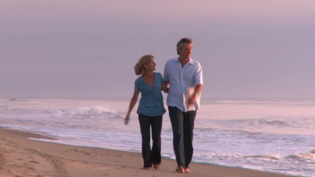 caucasian husband and wife walking toward camera along beach at sunrise - husband stock videos & royalty-free footage