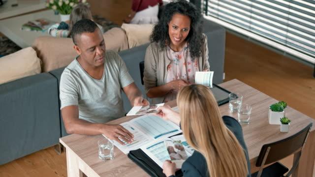 Caucasian insurance agent advising multi ethnic couple in their home