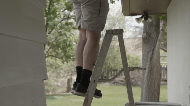 vidéos et rushes de adulte mâle caucasien escaladant une échelle pour accéder au toit de sa maison résidentielle - échelle